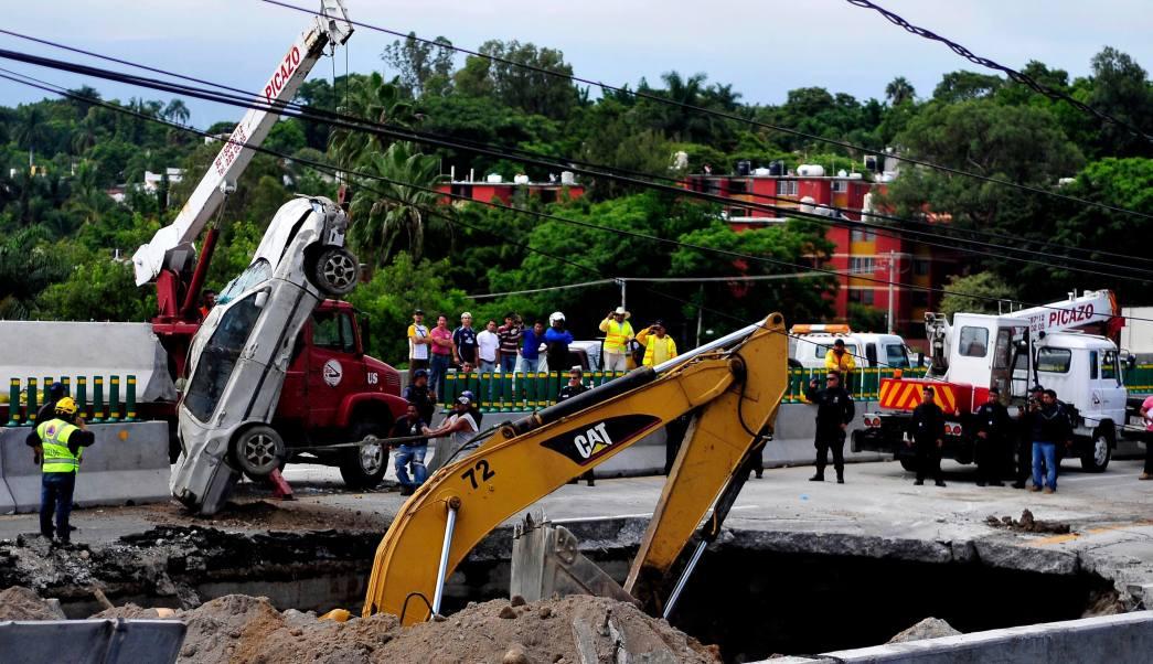 Maquinaria remueve tierra del socavón formado en el Paso Express