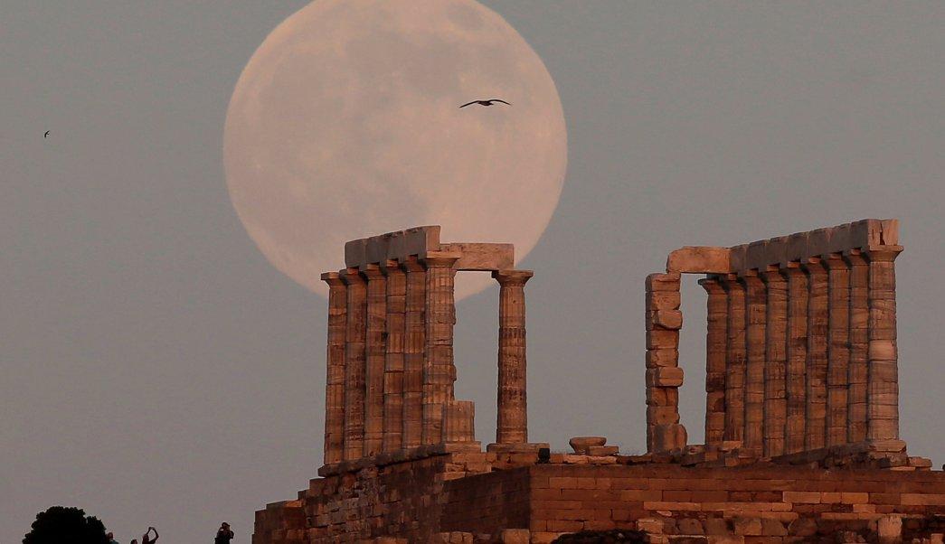 Luna llena se eleva sobre ruinas arqueológicas en Atenas