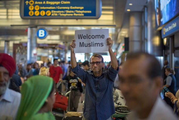 Un hombre lleva una señal de bienvenida a los viajeros que llegan a EU tras las prohibiciones del presidente Trump (Getty Images)
