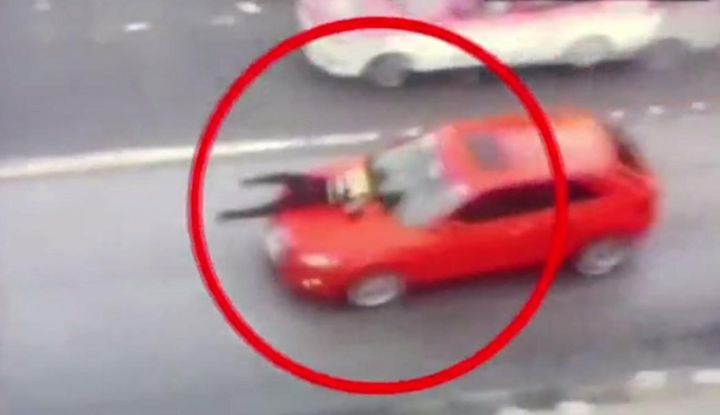 Policía se aferra al cofre de un vehículo. (Noticieros Televisa)