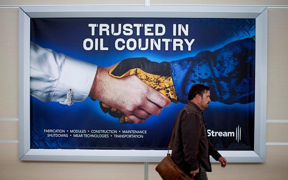 Hombre camina frente a un anuncio de petróleo canadiense
