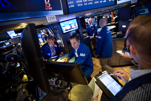 Brókers trabajan en el piso de la Bolsa de NY