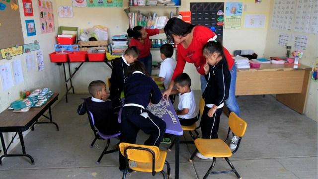maestra trabaja con alumnos en un salon