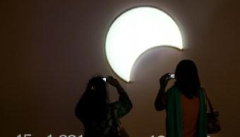 dos personas ven como evoluciona un eclipse