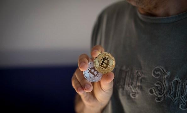 Un hombre muestra dos criptomonedas denominadas Bitcoin