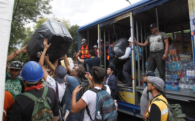 Mexicanos ayudan en la repartición de víveres. (EFE)