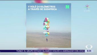Un hombre vuela con ayuda de cien globos de helio