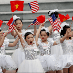 Niñas vietnamitas ondean banderas durante visita de Trump a Vietnam