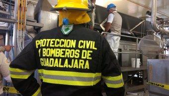 Bomberos laboran para rescatar a persona de procesadora de alimentos