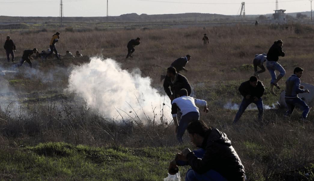 Palestinos corren ante el lanzamiento de gases lacrimógenos