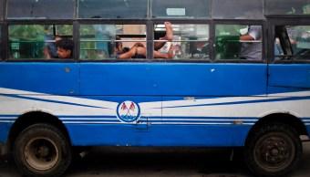 Pasajero con los pies de fuera en un autobús en India