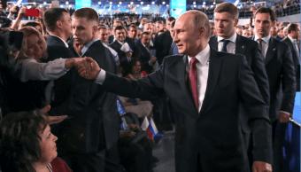 Putin saluda a varias personas durante un mitin en Moscú