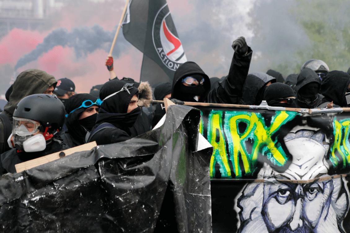 Activistas en Francia portan mascarillas y una imagen de Karl Marx. (AP)