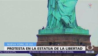 Mujer protesta sobre pedestal de la Estatua de la Libertad