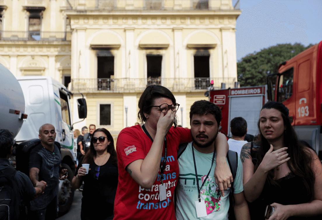 Funcionarios del Museo Nacional lloran tras el incendio en Río de Janeiro. (EFE)