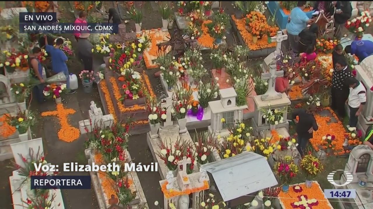 A pesar de la lluvia familias mexicanas visitan el panteón de Mixquic