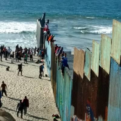 Integrantes de caravana migrante se trepan a valla fronteriza en Tijuana