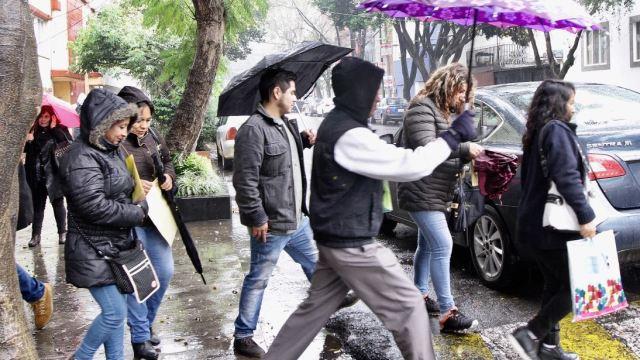 Un grupo de personas se protege de la lluvia, 12 mayo 2019