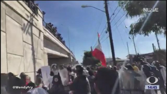 Migrante hondureño porta la bandera de México