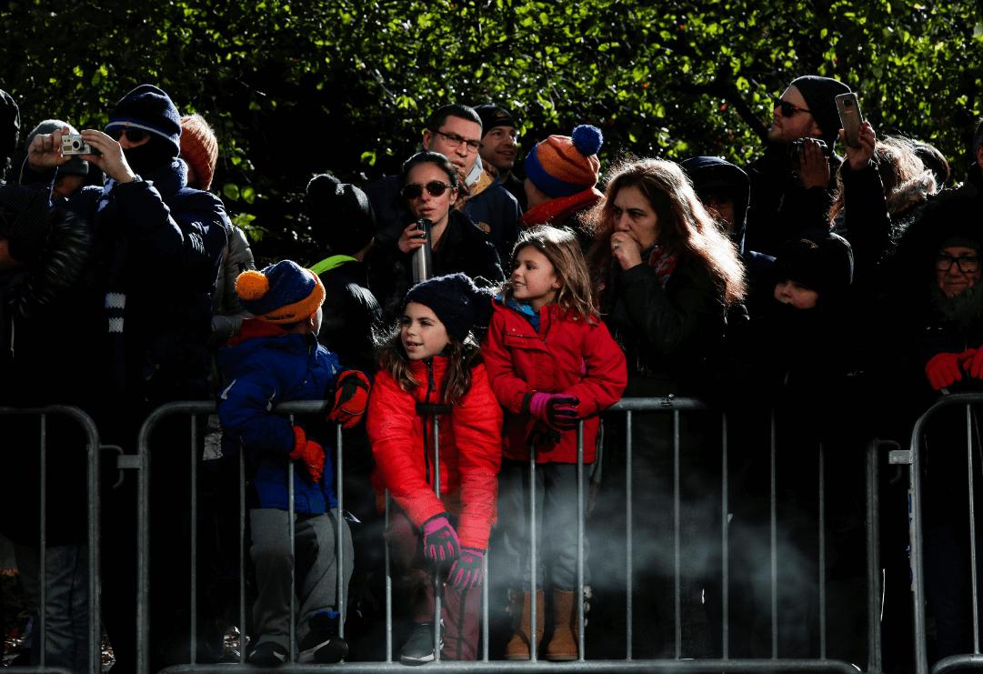 Personas disfrutan del desfile de Acción de Gracias. (AP)