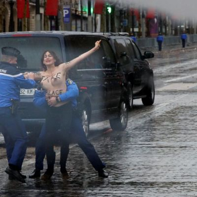 Manifestante protesta con el pecho desnudo ante convoy de Trump en París