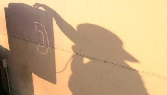La sombra de una persona que llama usando un teléfono público, 26 de enero 2019, (Getty Images)