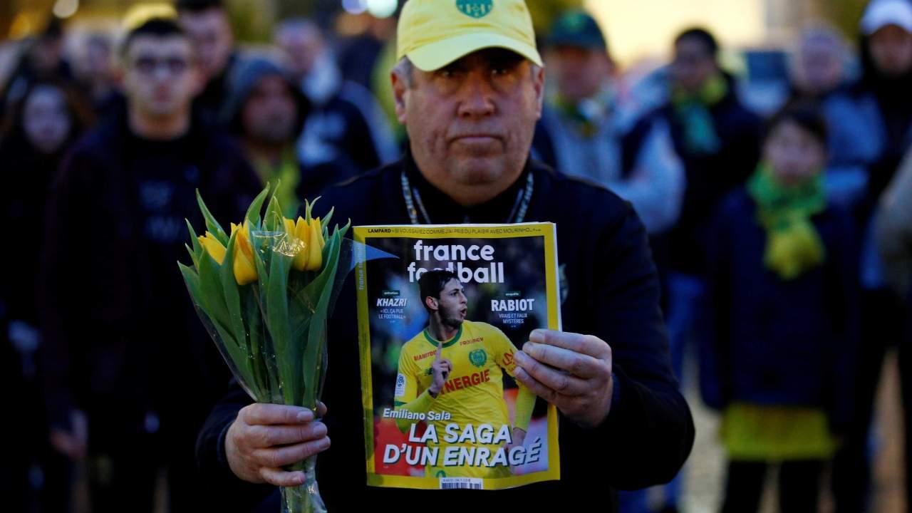 Foto: Seguidor del Nantes sostiene un ramo de flores y una revista con la imagen del futbolista argentino Emiliano Sala