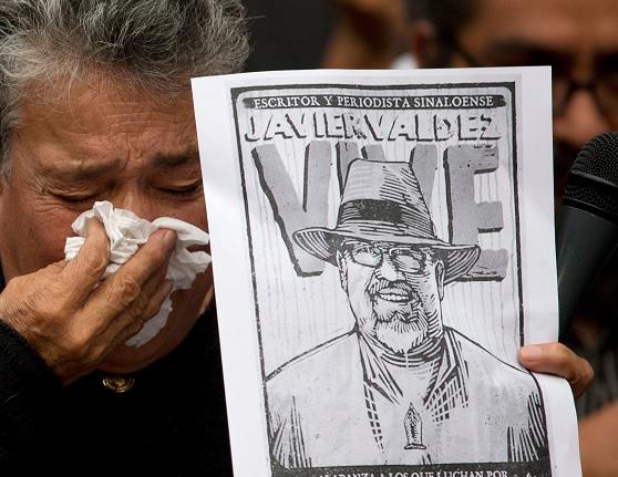 Foto: Una mujer activista sostiene un cartel con el rostro del periodista Javier Valdez el 16 de mayo del 2017. AP