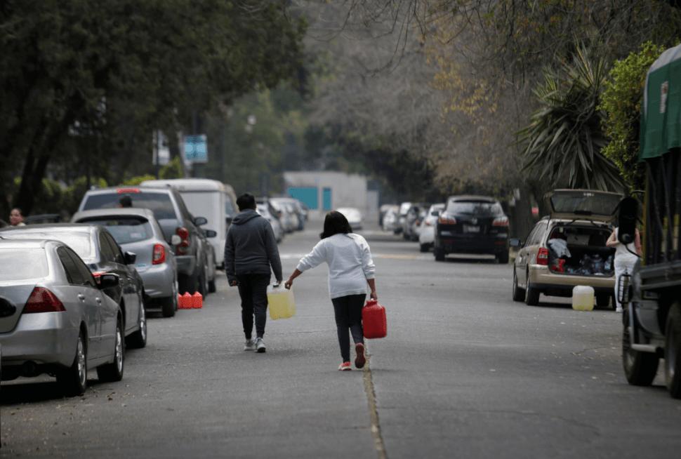 Personas cargan bidones con gasolina en México. (Reuters)