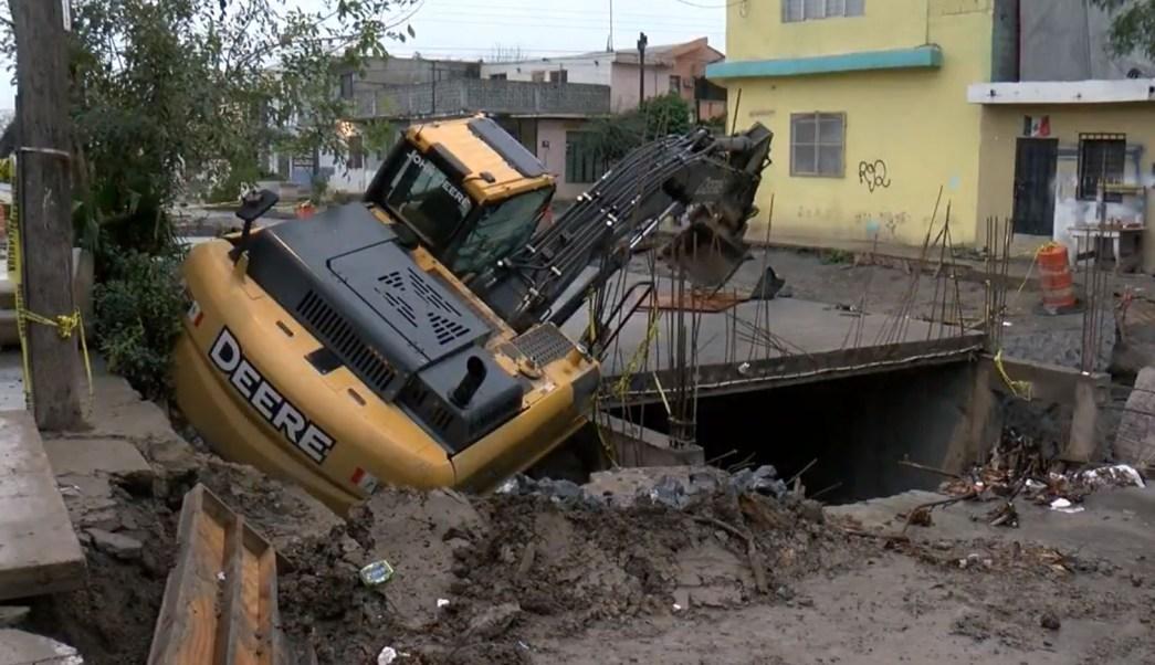 Corriente de lluvia arrastra retroexcavadora y cae en zanja en Monterrey