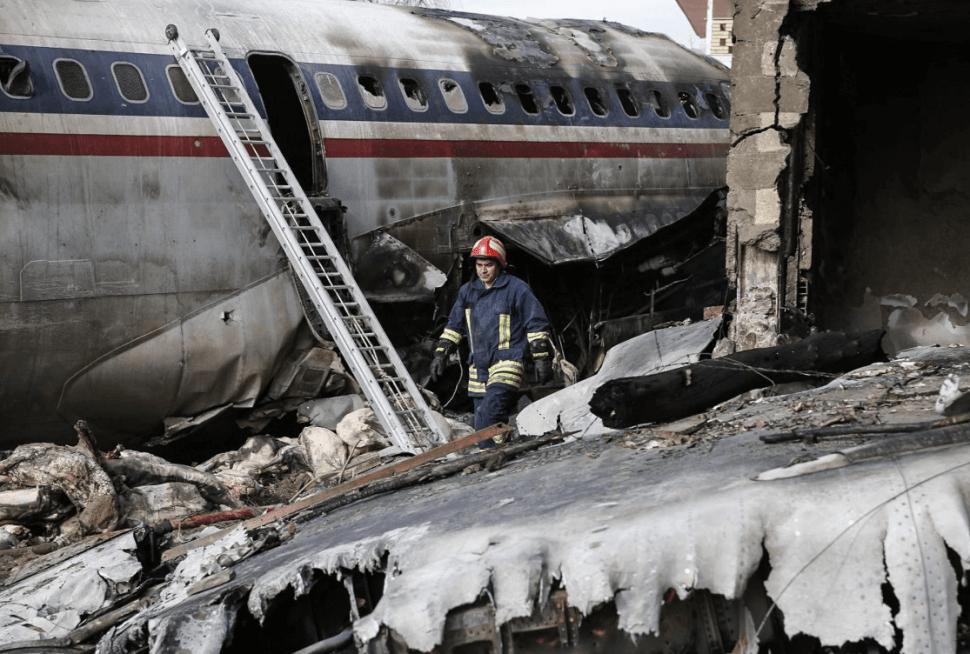Un hombre camina entre los restos del fuselaje de un avión accidentado en Irán. (EFE)