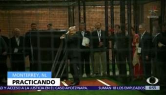 AMLO practica swing de béisbol, vestido de traje