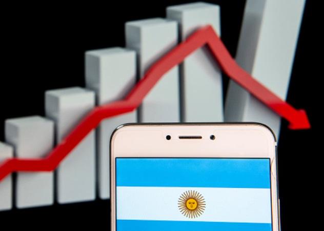 Foto: La bandera de Argentina se ve en un dispositivo móvil con un gráfico de pérdidas en el fondo, febrero 11 de 2019 (Getty Images)