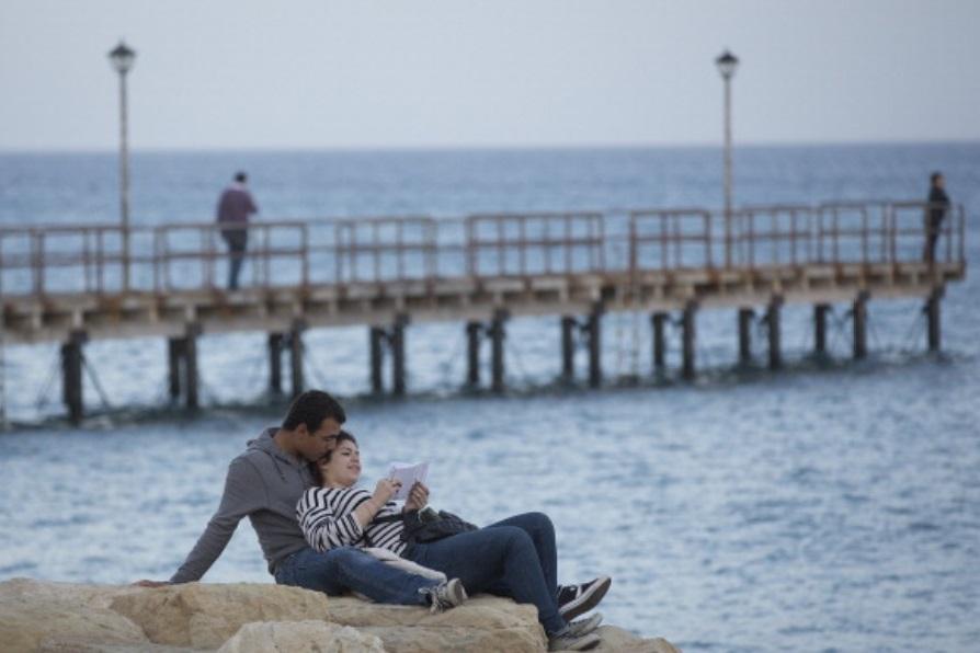 Foto: Una pareja se sienta en las rocas y mira hacia el mar, México, febrero 6 de 2019 (Getty Images)
