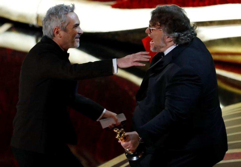 Foto: Guillermo del Toro (der) entrega a Alfonso Cuarón (der) el Oscar como mejor director, el 24 de febrero de 2019 (Reuters)