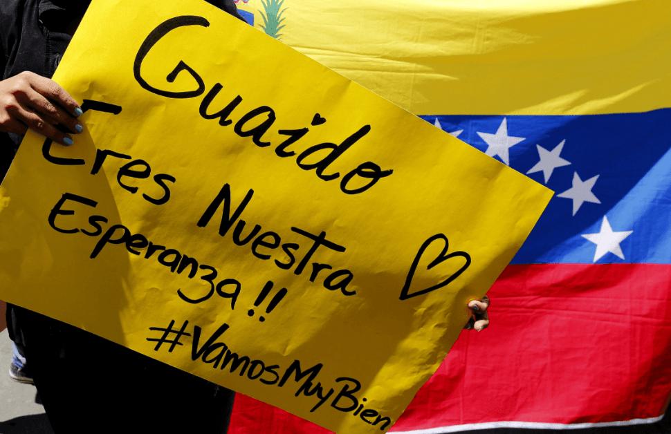 Foto: Una mujer sostiene un cartel de apoyo a Guaidó en Colombia, 25 de febrero de 2019