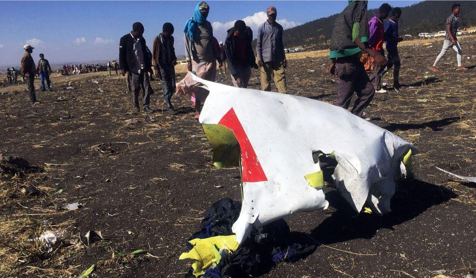 Foto: La gente pasa frente a una parte de los escombros en la escena del accidente aéreo de Ethiopian Airlines, 10 marzo 2019