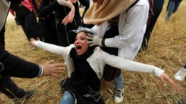 Foto: Mujer palestina reacciona después de inhalar gas lacrimógeno disparado por fuerzas israelíes durante una protesta en la Franja de Gaza, marzo 30 de 2019 (Reuters)