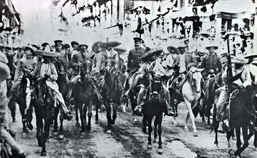 Los jefes de la División del Norte y del Ejército del Sur, los generales Pancho Villa y Emiliano Zapata, acompañados de los generales Tomás Urbina, Rodolfo Fierro, Rafael Buelna y otros más, a su paso por la avenida Plateros (hoy Madero), el 6 de diciembre de 1914, en la Ciudad de México. (CC/Wikimedia)