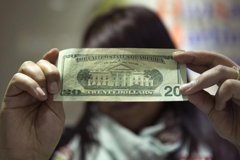 Foto: Un trabajador inspecciona un billete de veinte dólares de Estados Unidos en el Aeropuerto Internacional Benito Juárez en la Ciudad de México, abril 9 de 2019 (Getty Images)