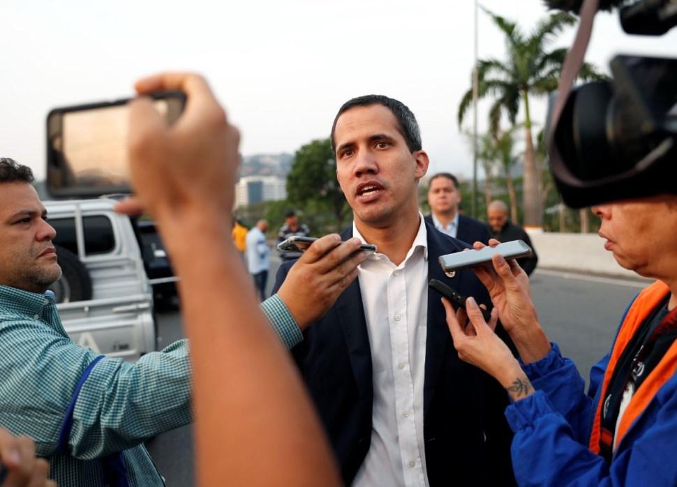 El líder opositor y presidente autoproclamado Juan Guaidó habla con medios de comunicación cerca de la base aérea militar 'La Carlota' en Caracas (Reuters)