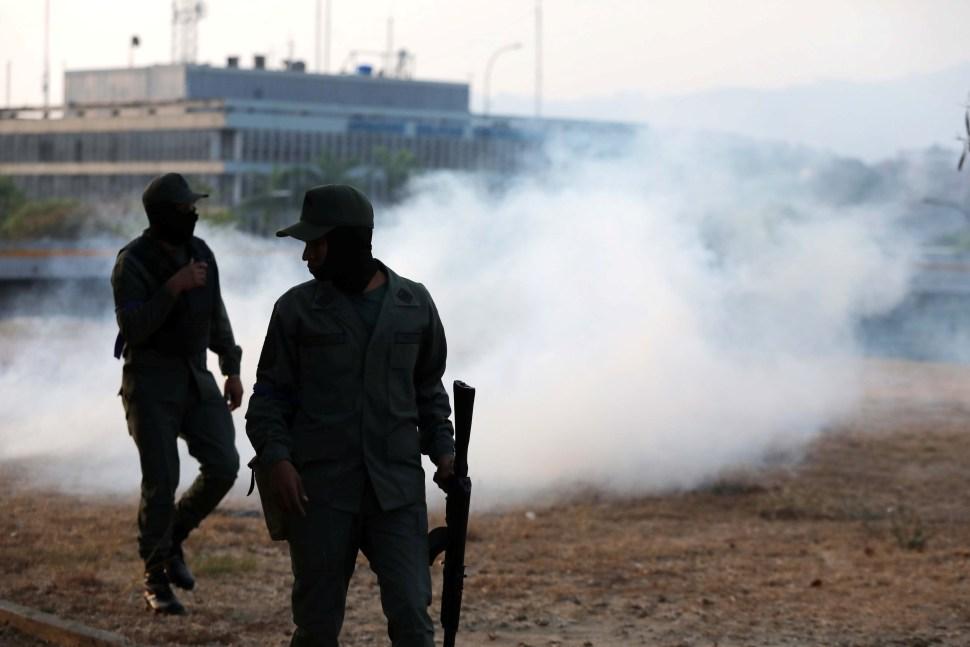 Flota gas lacrimógeno cerca de la concentración de militares y opositores políticos que se instalaron a las afueras de la base militar 'La Carlota' (Reuters)