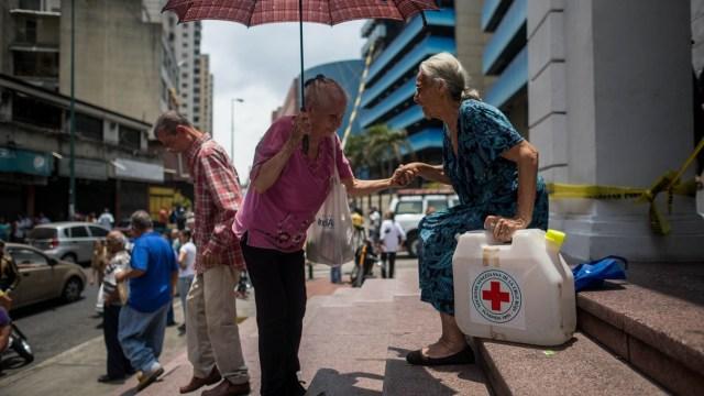 Foto: Dos ancianas cargan un bidón al salir de la sede de la Cruz Roja en Caracas, Venezuela. El 18 de abril de 2019