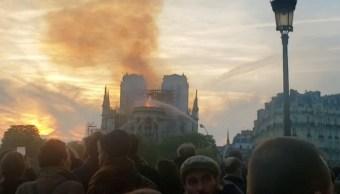 Foto: Las personas se reúnen mientras los bomberos rocían agua para extinguir las llamas mientras la catedral de Notre Dame arde en París, Francia, el 15 de abril de 2019 (Reuters)