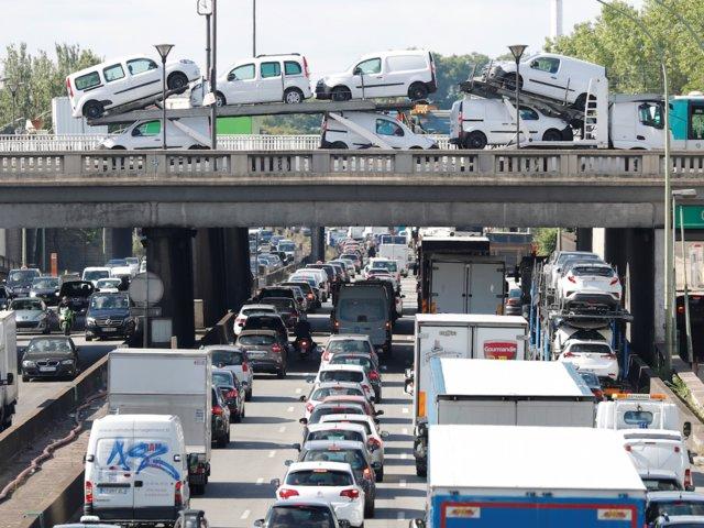 Un camión transporta vehículos sobre uno de los puentes que pasan sobre la autopista periférica de Paris (Reuters)