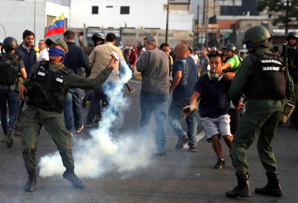 Un militar arroja de vuelta un cartucho de gas lacrimógeno disparado hacia la concentración de opositores políticos (Reuters)