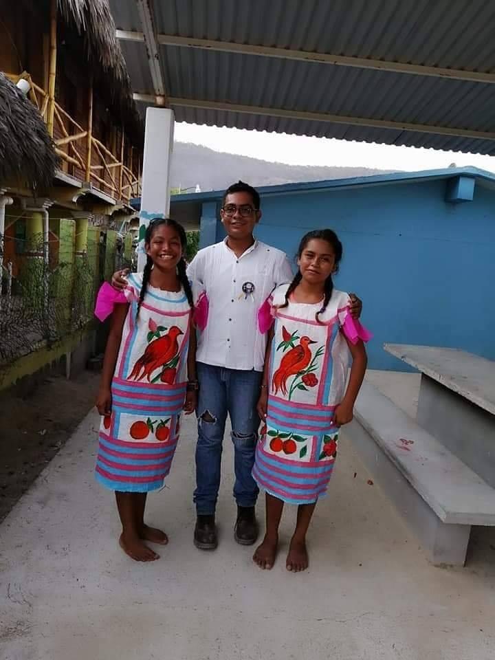 El maestro Armando Reyes posa al centro de la fotografía junto a dos alumnas que están usando sus huipiles hechos a mano (Facebook Cosas de oaxaqueños)