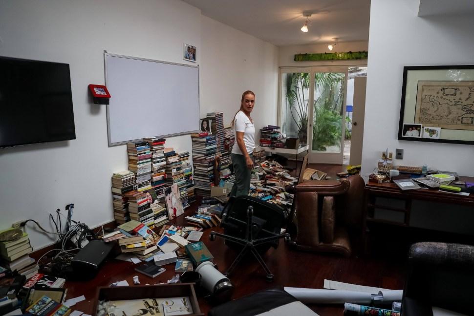Foto: Lilian Tintori, esposa de Leopoldo López, recoge libros tirados en su casa de Caracas, Venezuela. El 1 de mayo de 2019