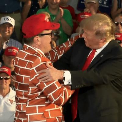 Hombre vestido de muro saluda a Trump en mitin