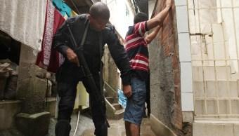 Foto: Un agente de la Policía de Brasil revisa a un joven en una favela de Río de Janeiro. El 8 de diciembre de 2009